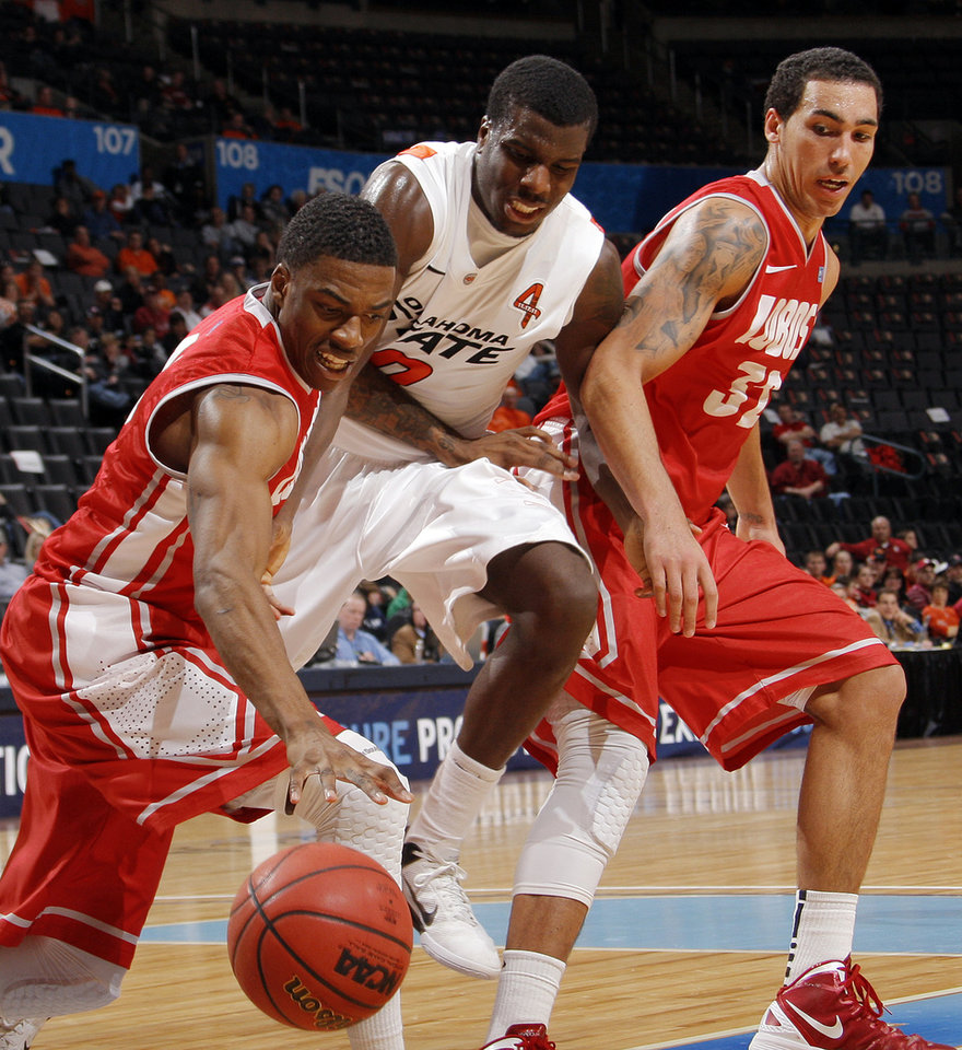 Photo - UNM's Demetrius Walker (40) takes the ball from OSU's Jean-Paul Olukemi (0) next to UNM's Drew Gordon (32) in the second half during the Bill Russell men's college basketball game of the Ramada All-College Classic between the Oklahoma State University Cowboys and the University of New Mexico Lobos at the Chesapeake Energy Arena in Oklahoma City, Sunday, Dec. 18, 2011. UNM beat OSU, 66-56. Photo by Nate Billings, The Oklahoman