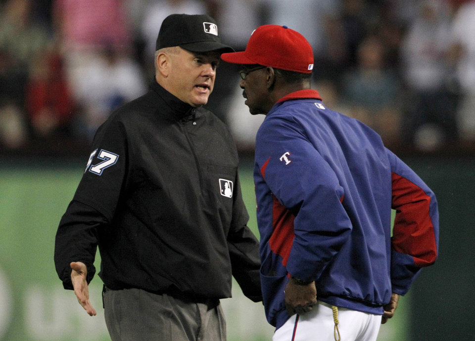 Photo -   Second base umpire Mike Everitt responds to an inquiry from Texas Rangers manger Ron Washington, right, on a Ian Kinsler hit that put him on second in the first inning of a baseball game against the Seattle Mariners Friday, Sept. 14, 2012, in Arlington, Texas. After officials reviewed the hit on video it was ruled a home run. (AP Photo/Tony Gutierrez)