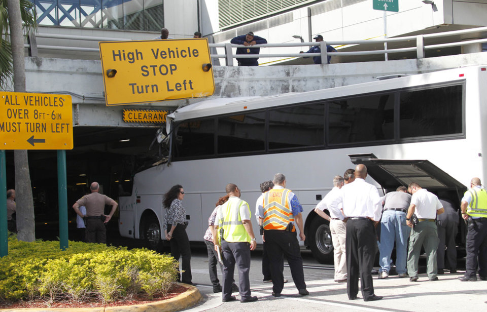 Photo - Workers and law enforcement officers prepare to remove a bus after it hit a concrete overpass at Miami International Airport in Miami on Saturday, Dec. 1, 2012. The vehicle was too tall for the 8-foot-6-inch entrance to the arrivals area, and buses are supposed to go through the departures area which has a higher ceiling, according to an airport spokesperson. (AP Photo/Wilfredo Lee)