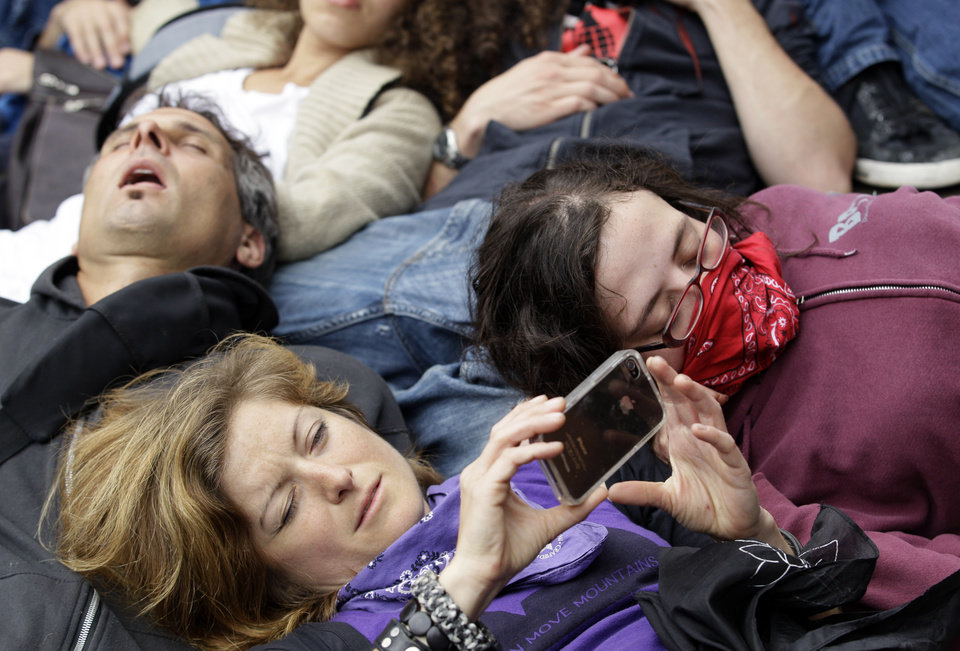 Photo -   A protester uses her phone during a die-in at Boeing corporate offices as a part of the NATO summit Monday, May 21, 2012 in Chicago. (AP Photo/Nam Y. Huh)