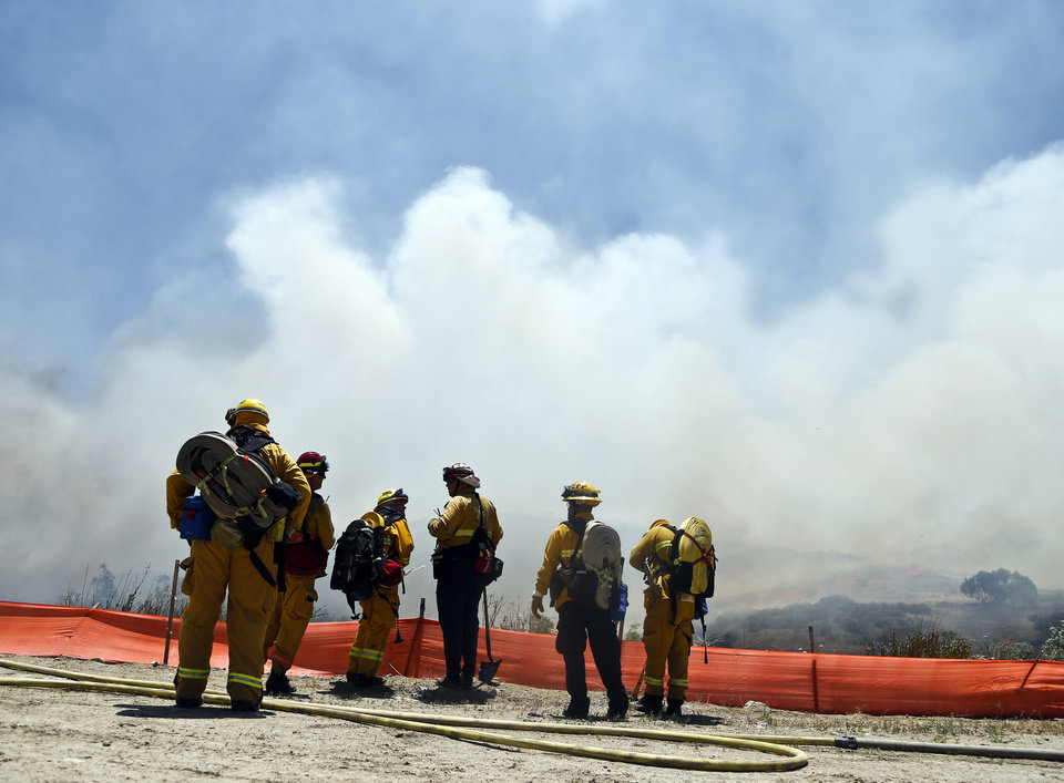 Photo - Firefighters face a huge smoke cloud as they plan their attack on a wild fire Tuesday, May 13, 2014, in San Diego. Wildfires destroyed a home and forced the evacuation of several others Tuesday in California as a high-pressure system brought unseasonable heat and gusty winds to a parched state that should be in the middle of its rainy season. (AP Photo)