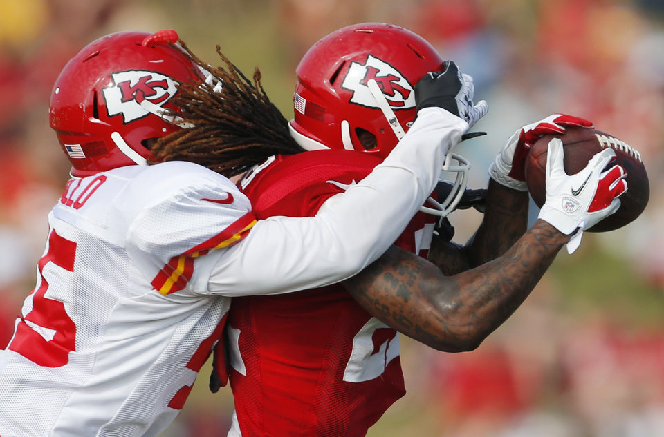 Kansas City Chiefs wide receiver Dexter McCluster (22) makes a catch while covered by defensive back Greg Castillo (45) during NFL football training camp in St. Joseph, Mo., Thursday, Aug. 1, 2013. (AP Photo/Orlin Wagner)