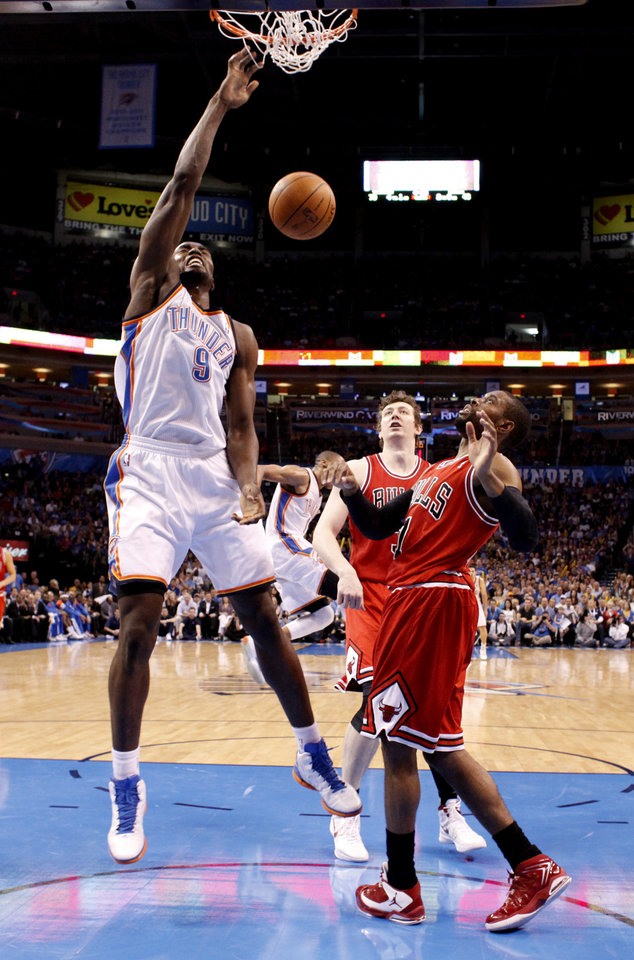 Photo - Oklahoma City's Serge Ibaka (9) dunks over Chicago's Omer Asik (3) and C.J. Watson (7) during the NBA basketball game between the Chicago Bulls and the Oklahoma City Thunder at Chesapeake Energy Arena in Oklahoma City, Sunday, April 1, 2012. Photo by Sarah Phipps, The Oklahoman