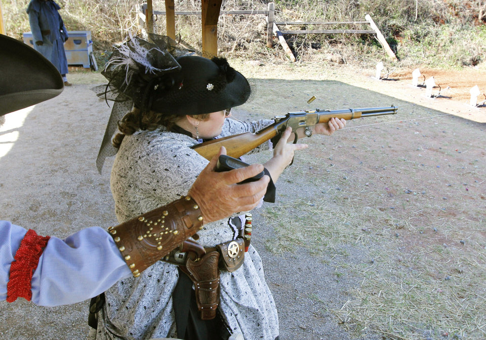 """Anita Bear"", aka Raemita Grubbs from Sand Springs, OK, shoots a lever action rifle during the Land Run, the biggest cowboy action shoot of the year Friday at the Oklahoma City Gun Club. Photo By Paul Hellstern, The Oklahoman"