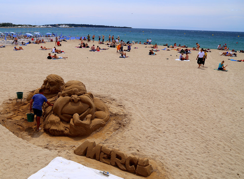 Photo - This picture taken May 11, 2014, shows a man working on a sand sculpture on a free beach in Cannes, one of several free attractions in this Riviera resort. Cannes is a favorite destination for the wealthy _ and for celebrities who walk the red carpet at the Cannes Film Festival each May _ but the Riviera resort also offers plenty of simple, inexpensive pleasures, from the beach to street strolls. (AP Photo/Michelle Locke)