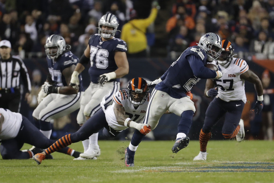 Photo - Dallas Cowboys' Ezekiel Elliott (21) runs out of a tackle of Chicago Bears' Ha Ha Clinton-Dix (21) during the first half of an NFL football game, Thursday, Dec. 5, 2019, in Chicago. (AP Photo/Morry Gash)