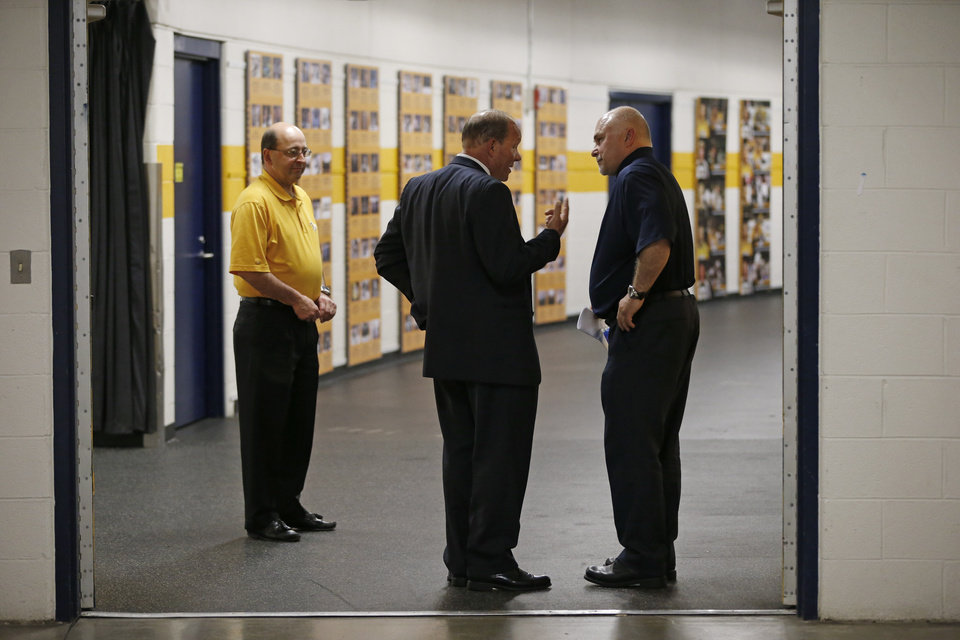 Photo - Nashville Predators head coach Barry Trotz, right, talks with Predators CEO Jeff Cogen, center, after Trotz appeared at a news conference Monday, April 14, 2014, in Nashville, Tenn. The Predators announced earlier in the day that Trotz's contract won't be extended and they will begin looking for a new head coach. Trotz is the only head coach the NHL hockey team has had. At left is Gerry Helper, Predators senior vice president of hockey communications and public relations. (AP Photo/Mark Humphrey)