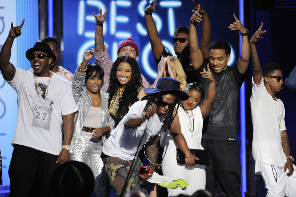 Photo - Lil' Wayne, center, slams the microphone onto the ground after Young Money is announced winner of the award for best group at the BET Awards at the Nokia Theatre on Sunday, June 29, 2014, in Los Angeles. (Photo by Chris Pizzello/Invision/AP)