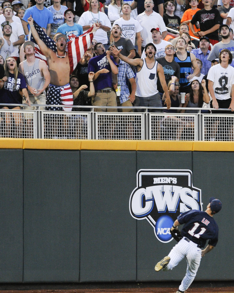 Photo - Mississippi left fielder Braxton Lee (11) watches fans celebrate a solo home run hit by TCU first baseman Kevin Cron (0) in the fifth inning of an NCAA baseball College World Series elimination game in Omaha, Neb., Thursday, June 19, 2014. (AP Photo/Eric Francis)