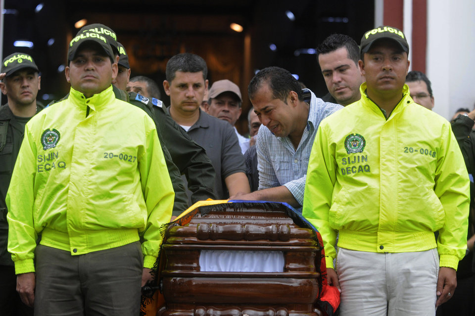 Relatives and fellow police officers carry the coffin containing the body of police officer Andres Rodriguez during his funeral service in Guarne, Colombia, Monday, April 30, 2012. Colombia's Defense Minister Juan Carlos Pinzon said his government has not launched any special rescue mission for Romeo Langlois, a French journalist who was accompanying a counterdrug mission when it was attacked by leftist rebels on Saturday, killing Rodriguez. (AP Photo/Luis Benavides)