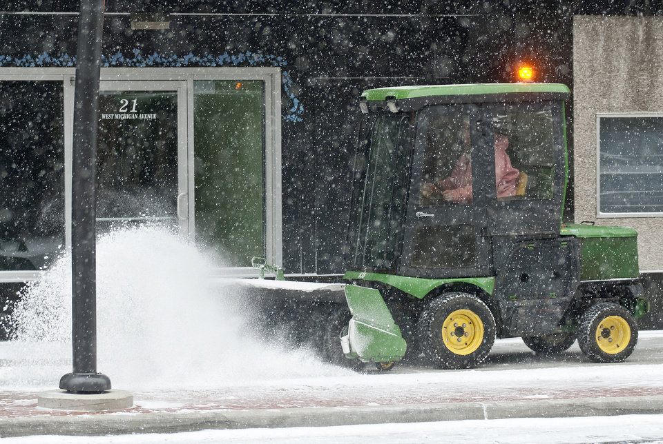 Photo - Crews from the City of Battle Creek, Mich.'s Field Services division clear the sidewalks in downtown as a snowstorm blanketed the area and whipped things up with high winds during the day Wednesday, Dec. 26, 2012. (AP Photo/Battle Creek Enquirer, Robert Youngs Jr.) NO SALES