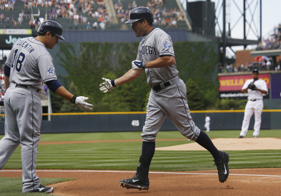 Photo - San Diego Padres' Carlos Quentin, left front, congratulates Seth Smith after he hit a solo home run off Colorado Rockies starting pitcher Juan Nicasio, back, in the first inning of a baseball game in Denver on Sunday, May 18, 2014. (AP Photo/David Zalubowski)