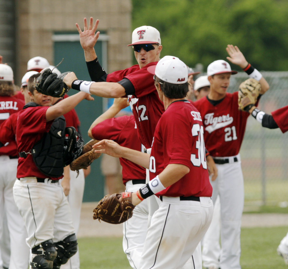 Photo - Tuttle players Zac Wall (22) and Dalton Secrist (30) jump in the air and bump shoulders after winning a Class 4A baseball state game between Edmond and Tuttle at Edmond SanteFe High School, Thursday, May 15, 2014, in Edmond. Photo by KT King, For The Oklahoman