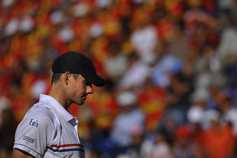 Photo -   John Isner of US, left, reacts after he lost a point during the second single match at Davis Cup World Group Semi-final tennis match against Nicolas Almagro, in Gijon, northern Spain, Friday, Sept. 14 , 2012. Almagro won the match 6-4, 4-6, 6-4, 3-6, 7-5. (AP Photo/Alvaro Barrientos)