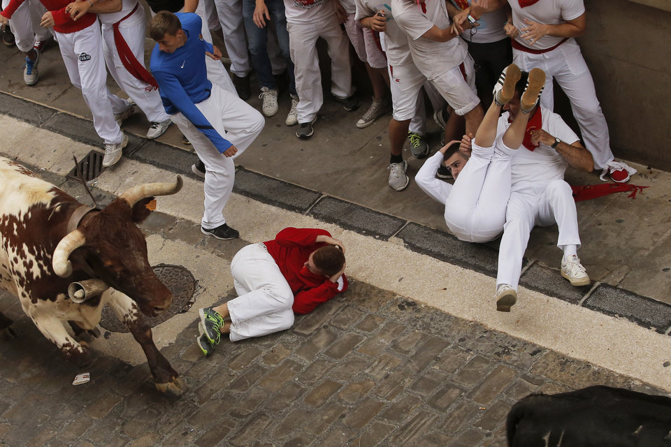 Photo - Revelers fall as Torrestrella fighting bull run during the running of the bulls of the San Fermin festival, in Pamplona, Spain, Monday, July 7, 2014. Revelers from around the world arrive to Pamplona every year to take part on some of the eight days of the running of the bulls glorified by Ernest Hemingway's 1926 novel