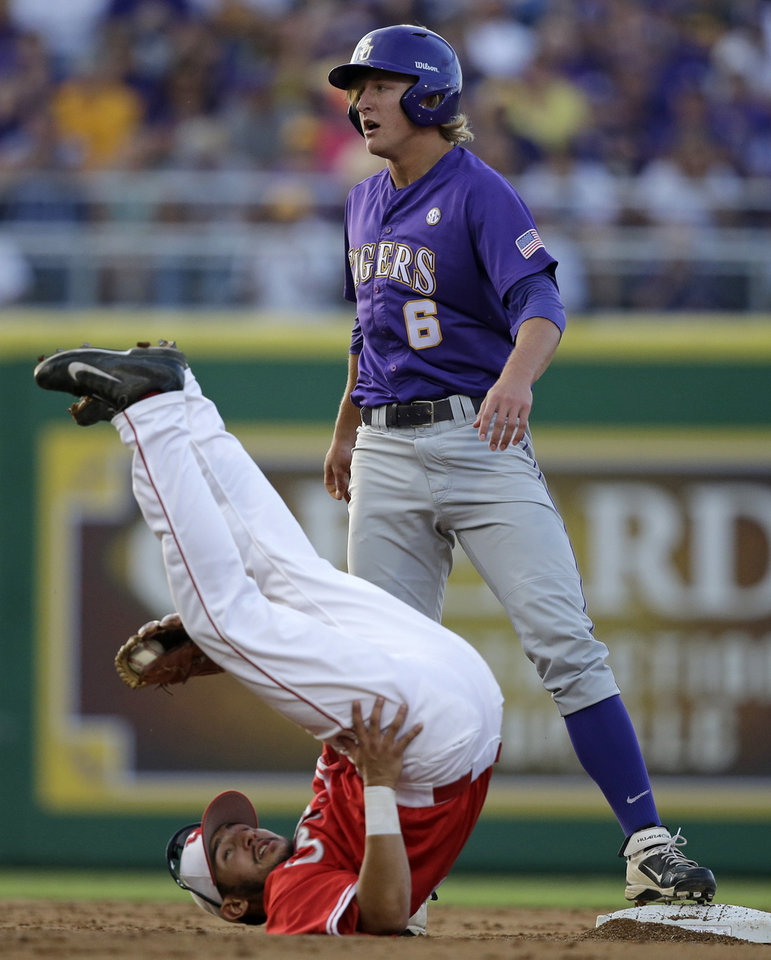Photo - Houston infielder Josh Vidales, left. rolls on his back after LSU's Andrew Stevenson, right,  steals second base in the second inning of an NCAA college baseball regional tournament game in Baton Rouge, La., Saturday, May 31, 2014. (AP Photo/Gerald Herbert)