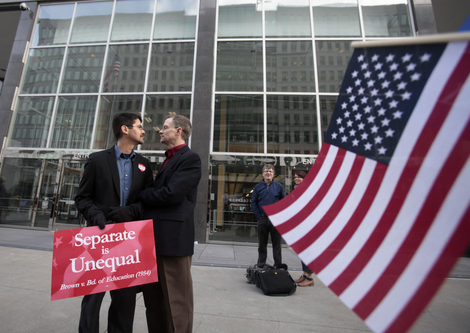 Photo - In this file photo from Jan. 11, 2010, Stuart Gaffney, left, and John Lewis, same-sex partners for 22 years, huddle outside of the federal courthouse in San Francisco. The U.S. Supreme Court decided Friday, Dec. 7, 2012, to hear the appeal of a ruling that struck down Proposition 8, the state's measure that banned same sex marriages. The highly anticipated decision by the court means same-sex marriages will not resume in California any time soon. The justices likely will not issue a ruling until spring of next year. A federal appeals court ruled in February that Proposition 8's ban on same-sex marriage was unconstitutional. But the court delayed implementing the order until same-sex marriage opponents proponents could ask the U.S. Supreme Court to review the ruling. (AP Photo/Marcio Jose Sanchez)