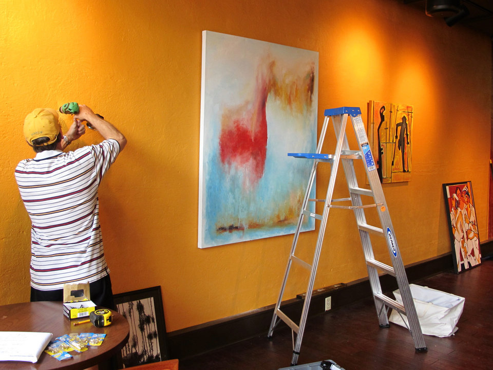 Photo - A worker hangs paintings at Table 118, a new restaurant in Lake City, S.C., as part of the ArtFields  arts festival on Thursday, April 18, 2013. The 10-day arts festival runs from April 19 through April 28, 2013. Many of the 400 works of art are being displayed in businesses in this old tobacco town. (AP Photo/Bruce Smith)