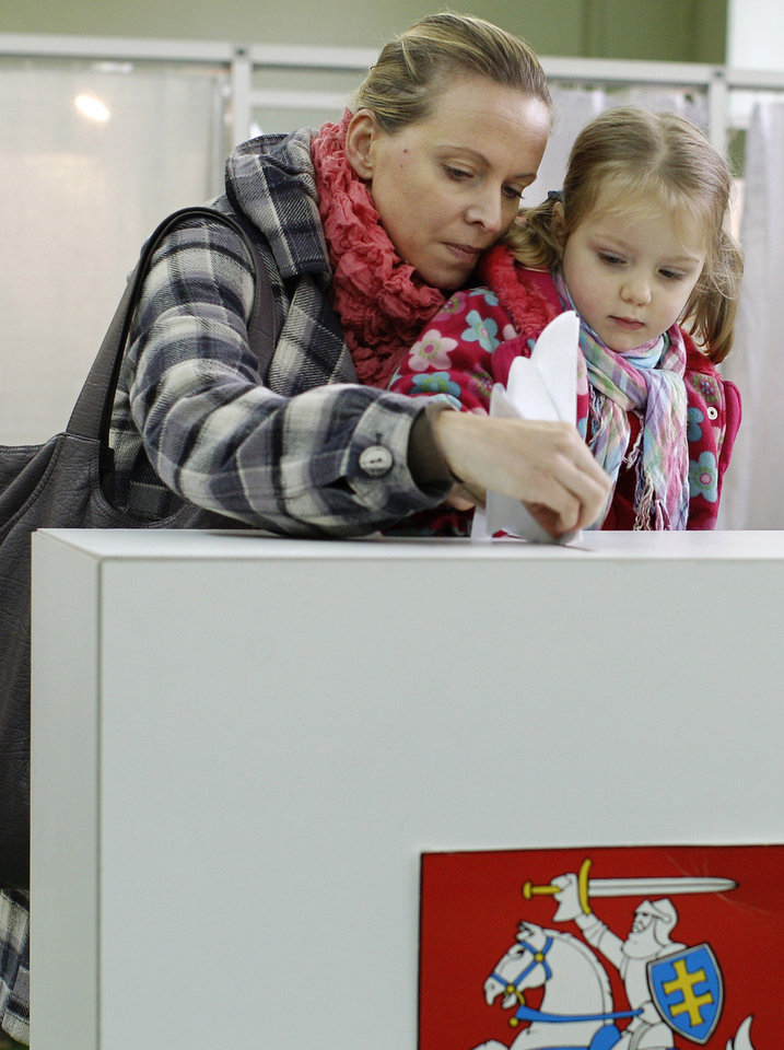 A woman with a child casts her ballot at a polling station in Vilnius, Lithuania, Sunday, Oct. 14, 2012. Lithuanians are expected to deal a double-blow to the incumbent conservative government in national elections Sunday by handing a victory to opposition leftists and populists and saying 'no' to a new nuclear power plant that supporters claim would boost the country's energy independence. (AP Photo/Mindaugas Kulbis)