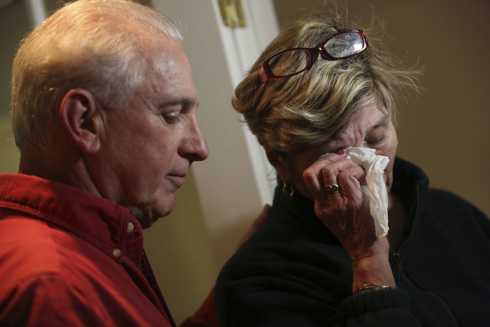 Photo - Ray Ruzek, left, consoles Shirley Towne as she speaks of the events of the day before a prayer meeting at the Heaven Ice Cream shop, Friday, Dec. 14, 2012 in Newtown, Conn. A gunman walked into the school Friday and opened fire, killing 26 people, including 20 children. (AP Photo/Mary Altaffer)