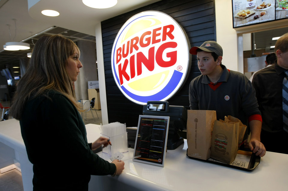 Photo - FILE - In a Saturday, Dec. 22, 2012 file photo, a customer purchases a meal at a Burger King restaurant in Marseille-Provence airport, in Marignane, France. Burger King is in talks to buy Tim Hortons in hopes of creating a new, publicly traded company with its headquarters in Canada. (AP Photo/Claude Paris, File)