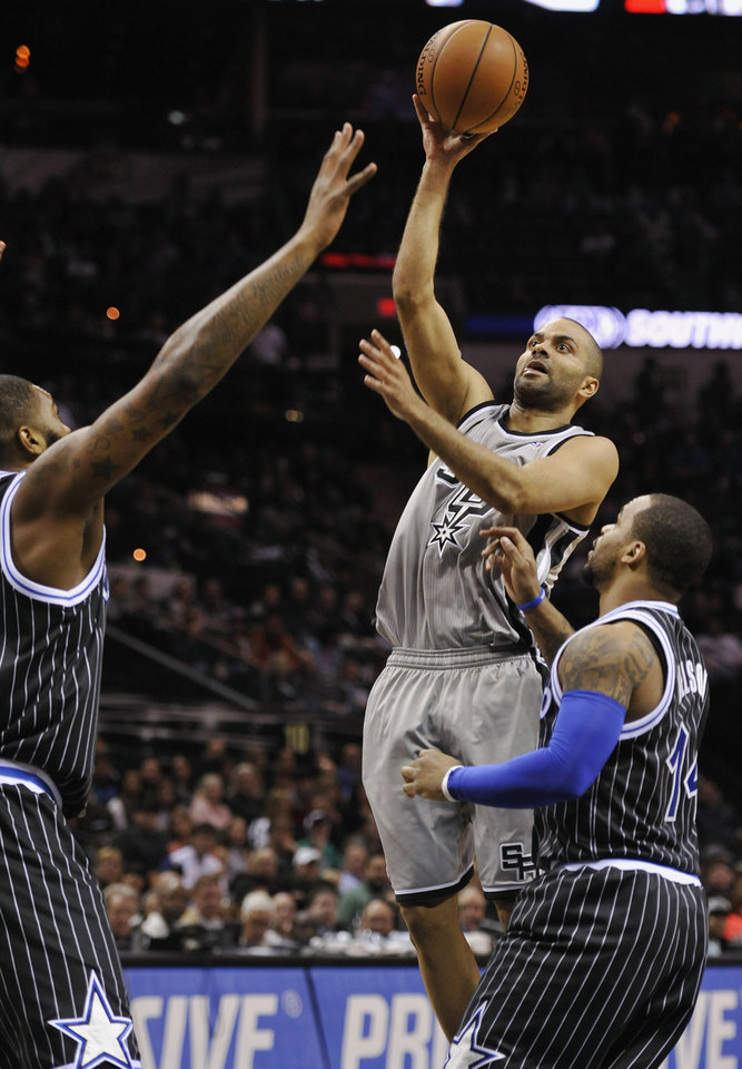 Photo - San Antonio Spurs guard Tony Parker, center, of France, shoots against Orlando Magic guard Jameer Nelson, right, and Magic forward Kyle O'Quinn, during the first half on an NBA basketball game on Saturday, March 8, 2014, in San Antonio. (AP Photo/Darren Abate)
