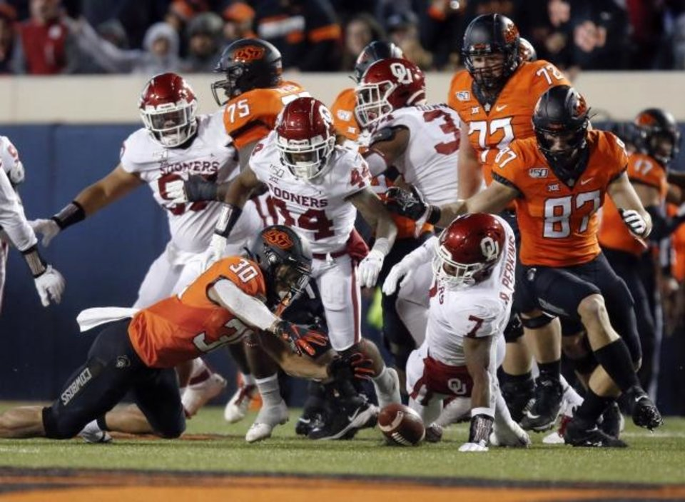 Photo -  Oklahoma State's Chuba Hubbard (30) recovers his own fumble in the second quarter during the Bedlam college football game between the Oklahoma State Cowboys (OSU) and Oklahoma Sooners (OU) at Boone Pickens Stadium in Stillwater, Okla., Saturday, Nov. 30, 2019. [Nate Billings/The Oklahoman]