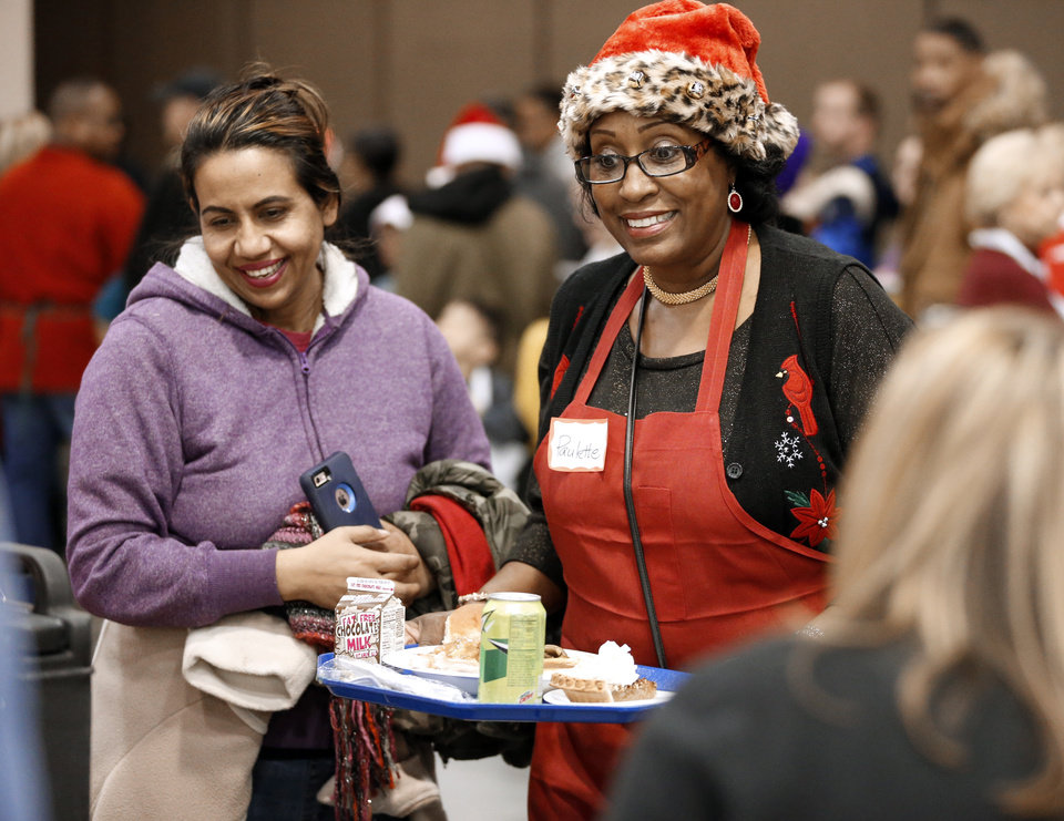 Photo -  Ten-year volunteer Paulette Anderson, right, helps Rardeea Hossein with her meal Monday during the Red Andrews Christmas Dinner. [Photo by Steve Sisney, The Oklahoman]