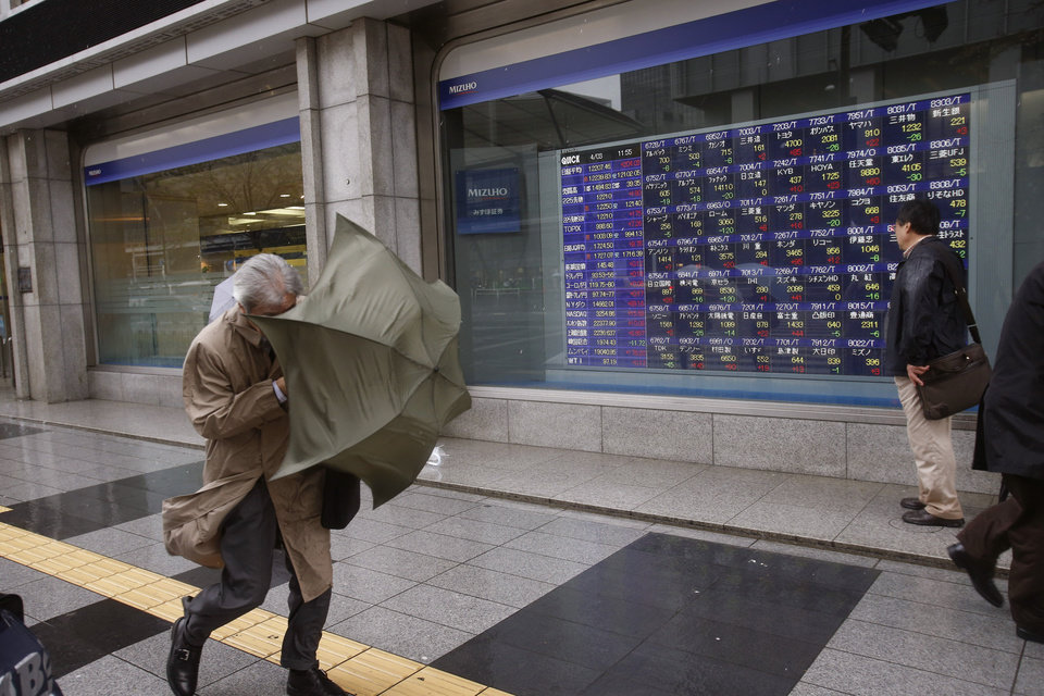 A man struggles to walk in the slanting rain in front of an electronic stock board in Tokyo Wednesday, April 3, 2013. Asian stock markets mostly rose Wednesday, boosted by more evidence the U.S. economic recovery is gaining traction. Japan's Nikkei 225 index in Tokyo jumped 1.7 percent to 12,207.46 as a fall in the yen enticed investors back into export shares. (AP Photo/Shizuo Kambayashi)