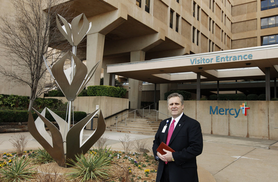 Photo - Deacon Paul Lewis, director of pastoral services at Mercy Hospital, stands at one of the hospital's entrance in Oklahoma City.   PAUL B. SOUTHERLAND - PAUL B. SOUTHERLAND
