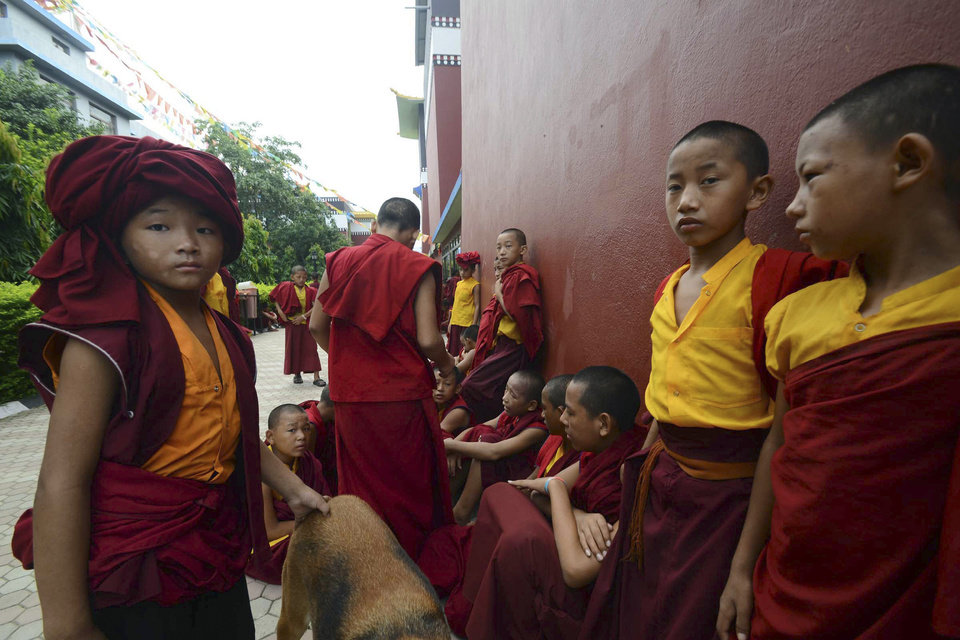 Novice Buddhist monks wait outside the Tergar Monastery, the site of an explosion, in Bodhgaya, about 130 kilometers (80 miles) south of Patna, the capital of the eastern Indian state of Bihar, Sunday, July 7, 2013. A series of small blasts hit three Buddhist temples in eastern India early Sunday, injuring at least two people, police said. (AP Photo/Manish Bhandari)