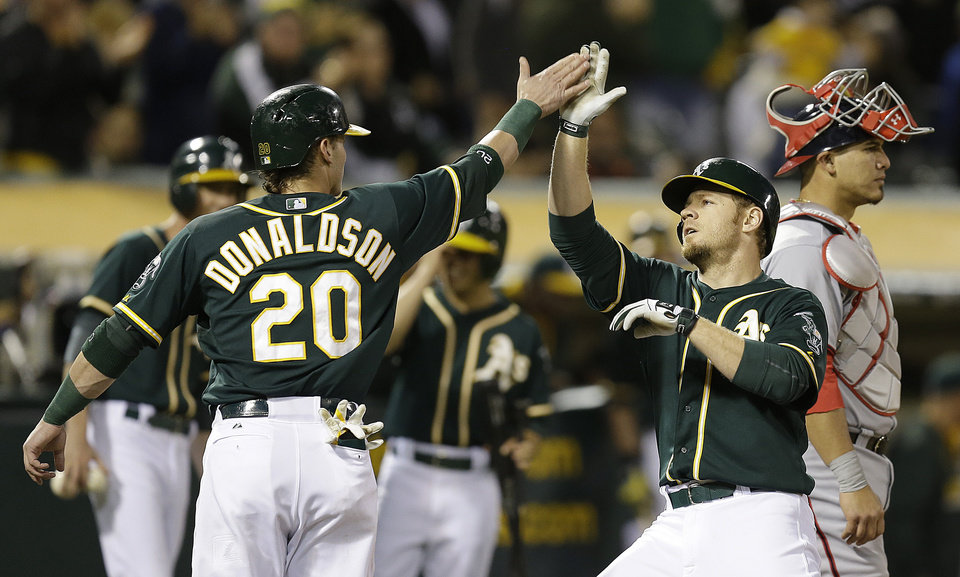 Photo - Oakland Athletics' Brandon Moss, front right, is congratulated by teammate Josh Donaldson (20) hitting a two-run home run off Washington Nationals' Doug Fister in the fifth inning of a baseball game on Friday, May 9, 2014, in Oakland, Calif. (AP Photo/Ben Margot)