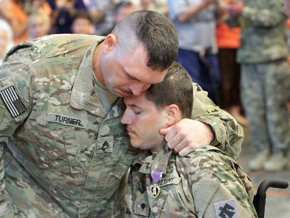 Photo -  Sergeant Darron Turner hugs Kevin Summerlin after Summerlin was awarded the Purple Heart during the welcome home ceremony. About 250 members of the The Oklahoma National Guard, 45th Infantry Brigade Combat Team (IBCT) returned from Afghanistan and Kuwait on Wednesday, March 28, 2012. Photo By David McDaniel/The Oklahoman
