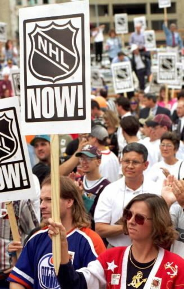 "1996 file photo  - Downtown workers raise an ""NHL NOW!"" sign during a rally in support of a National Hockey League expansion franchise for  Oklahoma  City. Photo by Jim Beckel"