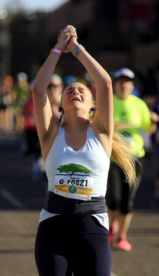 Photo - Sophia Wojcik reacts as she crosses the finish line to complete the half marathon during the Oklahoma City Marathon in Oklahoma City, Okla. on Sunday, April 29, 2018.  . Photo by Chris Landsberger, The Oklahoman