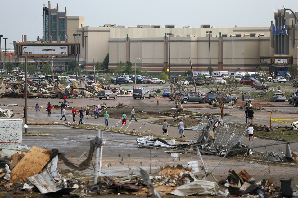 People walk through the parking lot of the Warren Theatre after it was damaged by a Moore, Okla., after a tornado moved through the area on Monday, May 20, 2013. Photo by Bryan Terry, The Oklahoman