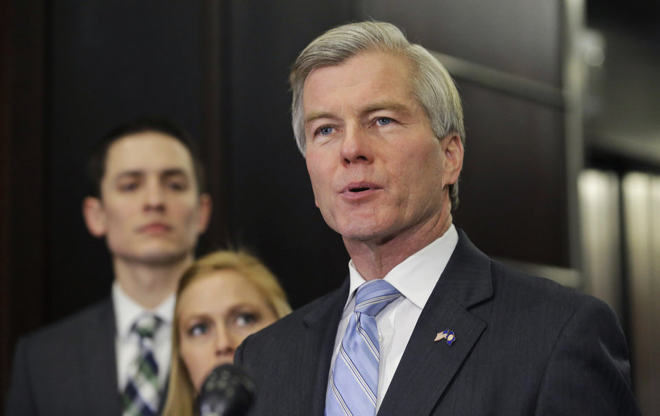 Photo - Former Virginia Gov. Bob McDonnell makes a statement as his daughter, Cailin and her husband, Chris Young, listen during a news conference in Richmond, Va., Tuesday, Jan. 21, 2014.  McDonnell and his wife were indicted Tuesday on corruption charges after a monthslong federal investigation into gifts the Republican received from a political donor.  (AP Photo/Steve Helber)