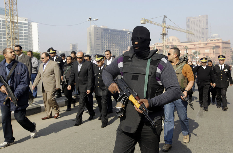 Photo - An Egyptian masked policeman guards Cairo's state security chief, Osama al-Saghir, third left, as he visits Tahrir Square, the epicenter of the 2011 uprising, in Cairo, Egypt, Saturday, Jan. 25, 2014. Demonstrators began gathering Saturday in Egypt's Tahrir Square to mark the third anniversary of the start of its 2011 revolution, though streets remained empty elsewhere in a city on edge following a spate of bombings claimed by militants.(AP Photo/Amr Nabil)
