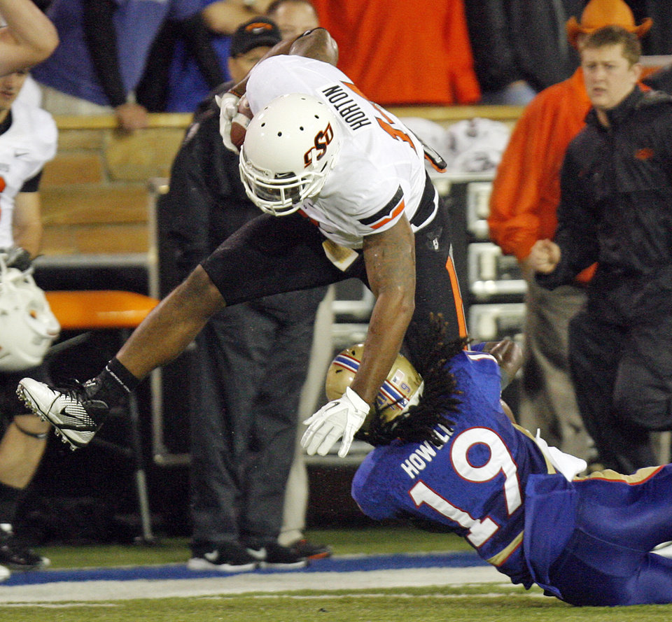 Photo - OSU's Justin Horton (14) is tackled by Milton Howell (19) of TU in the second quarter during a college football game between the Oklahoma State University Cowboys and the University of Tulsa Golden Hurricane at H.A. Chapman Stadium in Tulsa, Okla., Sunday morning, Sept. 18, 2011. Photo by Nate Billings, The Oklahoman