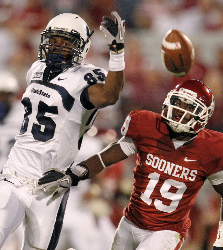 Photo - OU's Demontre Hurst defends Utah State's Dontel Watkins during the second half of the college football game between the University of Oklahoma Sooners (OU) and Utah State University Aggies (USU) at the Gaylord Family-Oklahoma Memorial Stadium on Saturday, Sept. 4, 2010, in Norman, Okla.   Photo by Bryan Terry, The Oklahoman