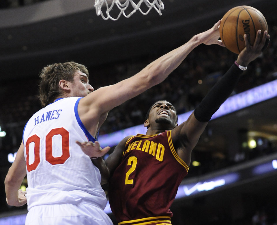 Philadelphia 76ers' Spencer Hawes (00) blocks a shot from Cleveland Cavaliers' Kyrie Irving (2) during the first half of an NBA basketball game on Sunday, Nov. 18, 2012, in Philadelphia. (AP Photo/Michael Perez)