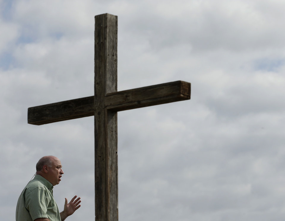 Pastor John Crowder talks to his congregation during a service for the First Baptist Church held in a field Sunday, April 21, 2013, four days after an explosion at a fertilizer plant in West, Texas. The church could not meet in their building because it was in a damage zone after a massive explosion at the West Fertilizer Co. Wednesday night that killed 14 people and injured more than 160. (AP Photo/Charlie Riedel)