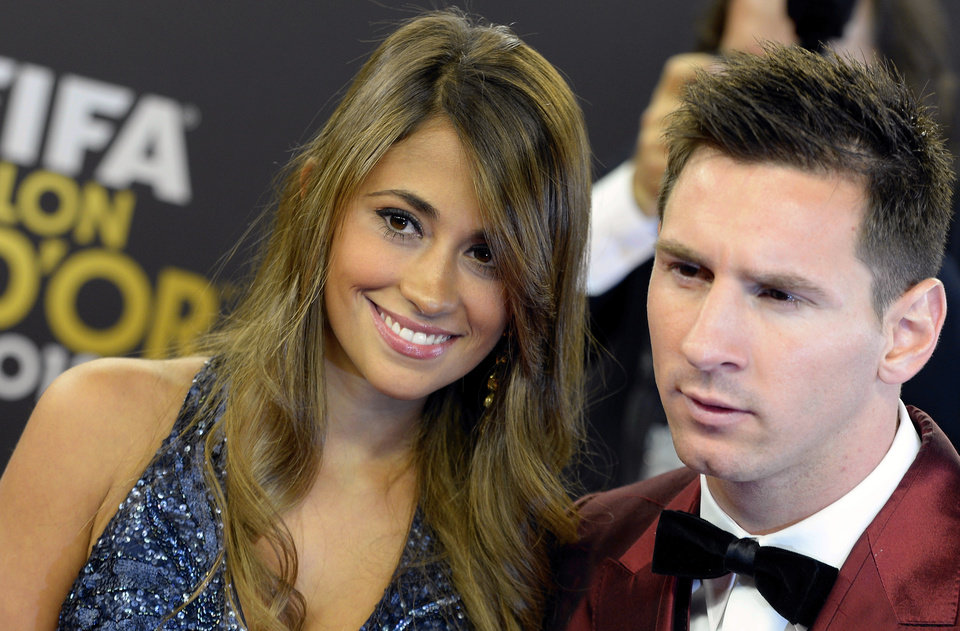 Photo - Soccer player Lionel Messi, right, of Argentina arrives with his wife Antonella, left, on the red carpet prior to the FIFA Ballon d'Or 2013 gala held at the Kongresshaus in Zurich, Switzerland, Monday, Jan. 13, 2014. (AP Photo/Keystone,Walter Bieri)
