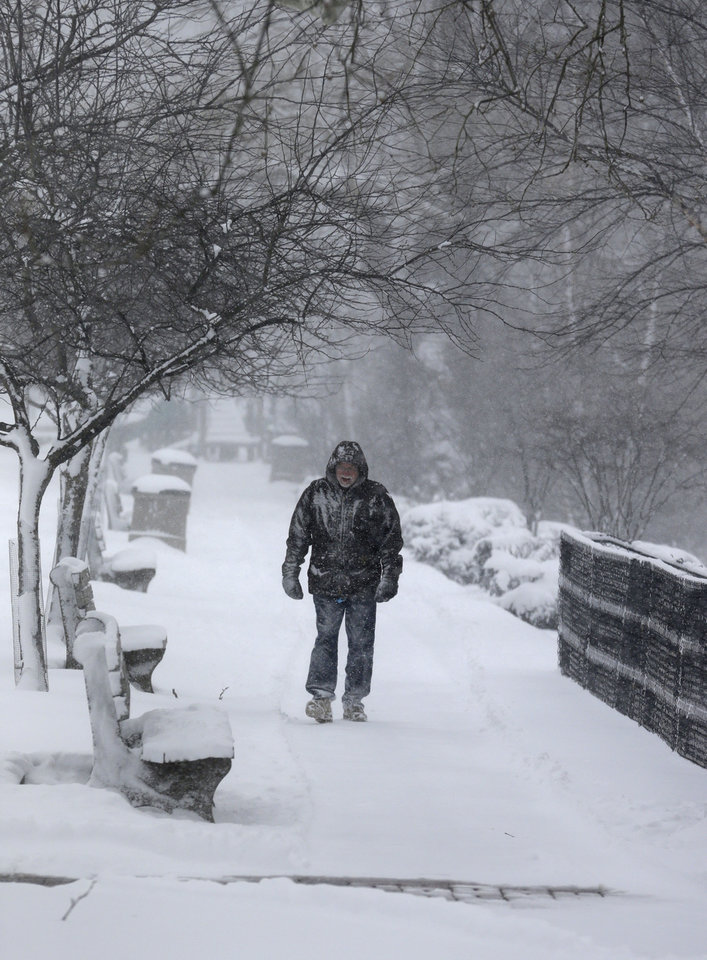 Bill Hart, 63, walks about two miles in the blowing snow Friday, Feb. 1, 2013, in Chagrin Falls, Ohio. Temperatures in northeast Ohio will remain in the teens Friday with a possiblility of  3 to 5 inches of new snow in areas. (AP Photo/Tony Dejak)
