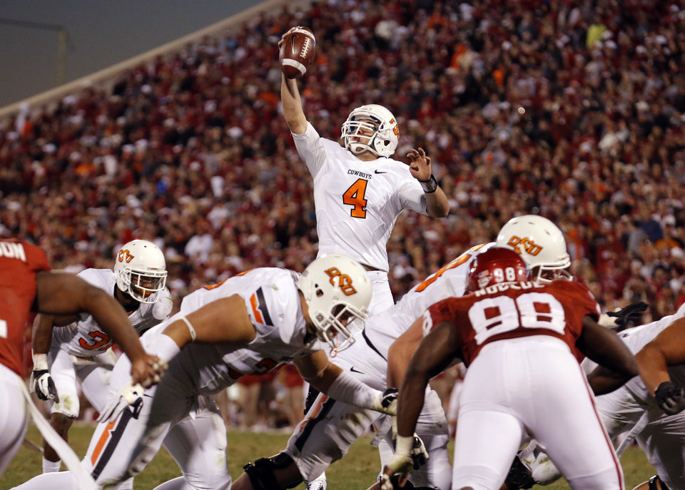 Oklahoma State\'s J.W. Walsh (4) grabs a high hike during the Bedlam college football game between the University of Oklahoma Sooners (OU) and the Oklahoma State University Cowboys (OSU) at Gaylord Family-Oklahoma Memorial Stadium in Norman, Okla., Saturday, Nov. 24, 2012. OU won 51-48 in overtime. Photo by Sarah Phipps, The Oklahoman