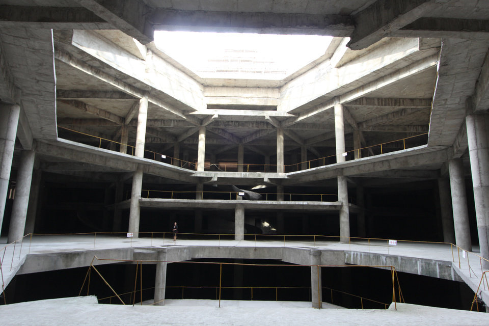 Photo -   In this Sept. 23, 2012 photo released by Koryo Group on Wednesday, Sept. 26, 2012, a visitor, center left, stands on the ground floor of the 105-story Ryugyong Hotel in Pyongyang, North Korea. After years of standing unfinished, construction on the exterior of the massive hotel resumed three years ago but the hotel has not yet opened to the public. This photo taken by the Beijing-based Koryo Tours shows that the interior remains unfinished. (AP Photo/Koryo Group) NO SALES, EDITORIAL USE ONLY