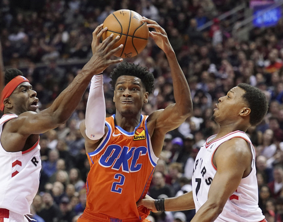 Photo - Oklahoma City Thunder Shai Gilgeous-Alexander (2) battles Toronto Raptors Terence Davis II (0) and Kyle Lowry (7) during fourth quarter NBA basketball action in Toronto on Sunday, Dec. 29, 2019. (Hans Deryk/The Canadian Press via AP)