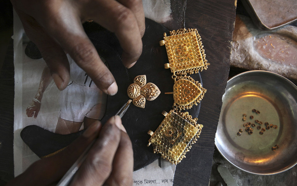 Photo - FILE - In this Aug. 29, 2013 file photo, an Indian goldsmith makes jewelry in Gauhati, India. Gold is India's second-biggest import behind oil, and purchases have soared in recent years as Indian incomes have risen. This increase in buying has had a negative impact on the economy, increasing the flow of money out of the country, and weakening the currency.(AP Photo/Anupam Nath, File)