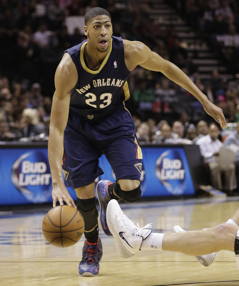 Photo - New Orleans Pelicans' Anthony Davis (23) drives to the basket against the San Antonio Spurs during the first half of an NBA basketball game, Monday, Nov. 25, 2013, in San Antonio. (AP Photo/Eric Gay)