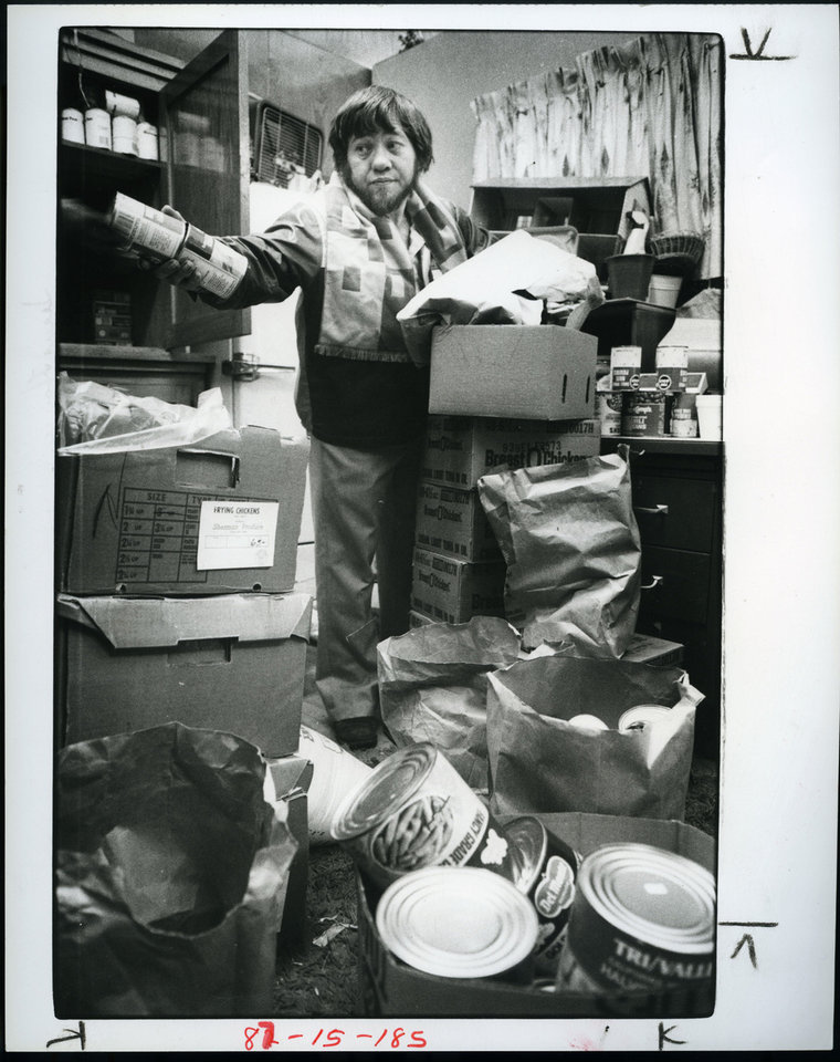 In this 1983 photograph, Ted O'Dell, Jesus House assistant director, hands out cans of food at the homeless shelter. <strong>PAUL S. HOWELL - STAFF</strong>